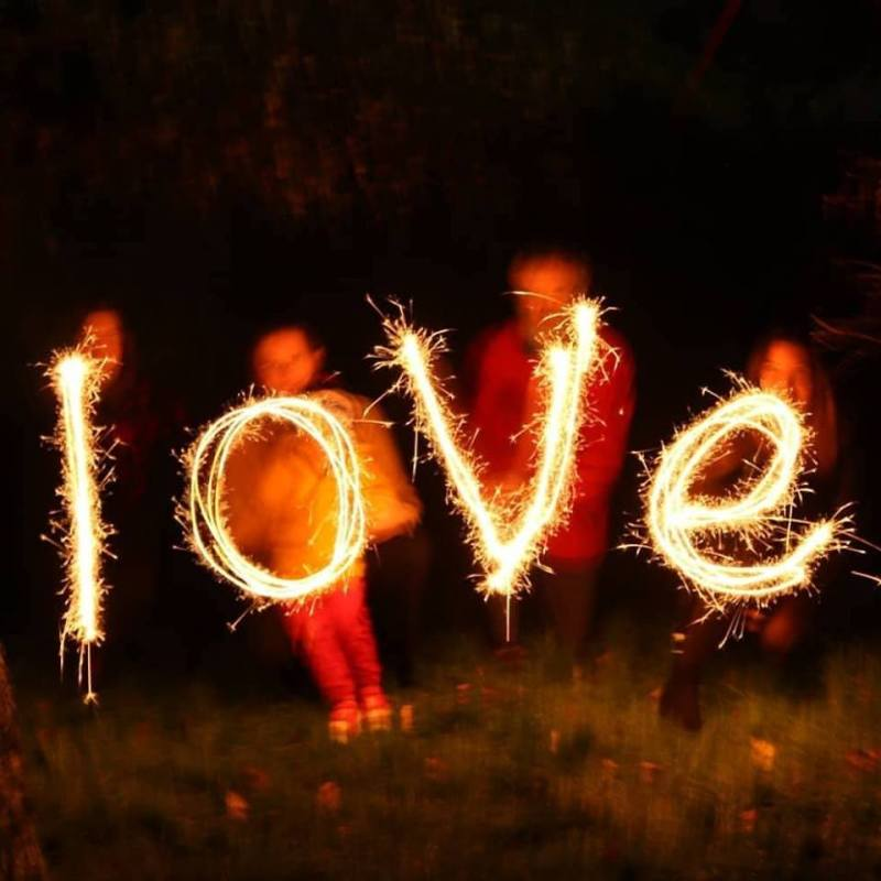 Four indistinct figures wave sparklers to spell the word LOVE